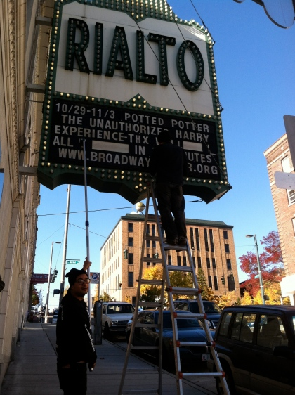 View across the street: changing out the marquee at the Rialto Theater, a landmark since 1922.